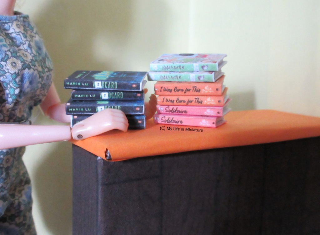 Ten books sit stacked in two piles on the orange countertop in The Palace Library. Sarah's hands are visible around one of the stacks.
