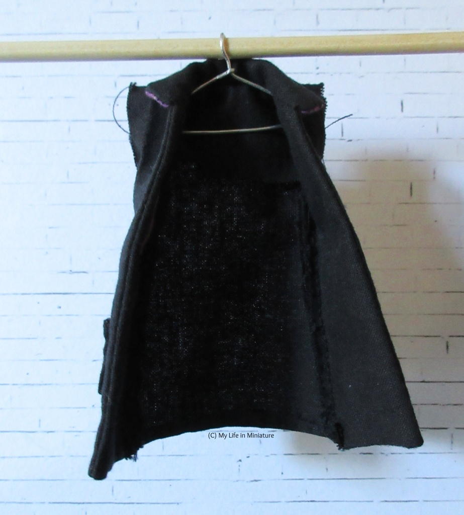 A black coat, unlined and sleeveless, hangs on a coat-hanger from a wooden dowel.