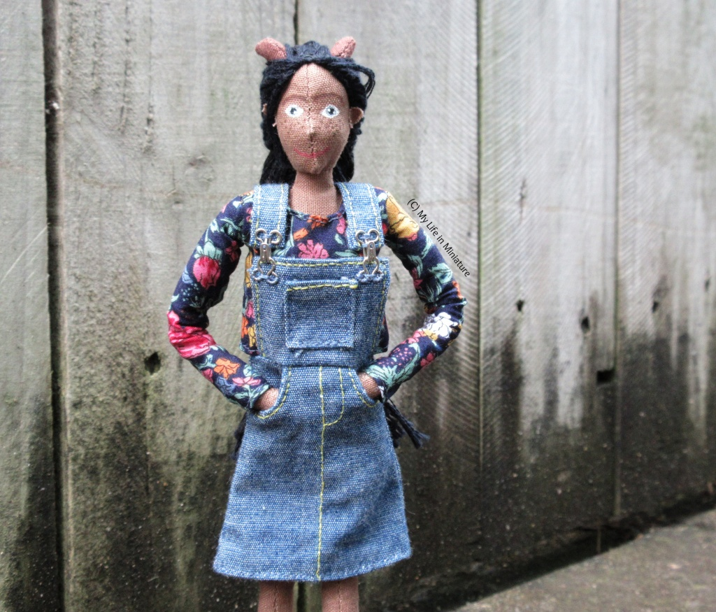 Petra wears her navy floral long-sleeved top under her denim pinafore dress, hands in pockets and smiling at the camera. She is outside, against a wooden fence.