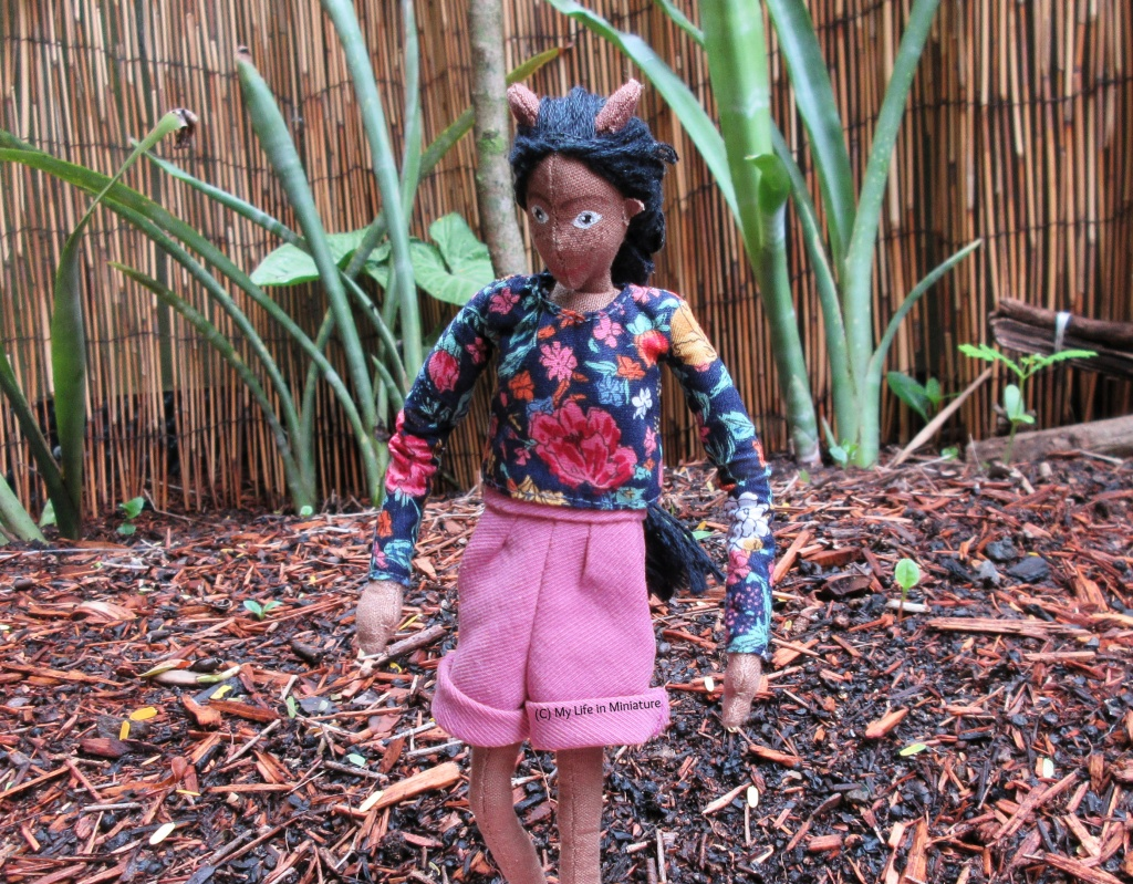 Petra wears her navy floral long-sleeved top with pink corduroy shorts. She is outside, on wet, partially-mulched ground, with tall green plants in the background. She is walking down a slope - arms out to balance, and looking down at her feet.