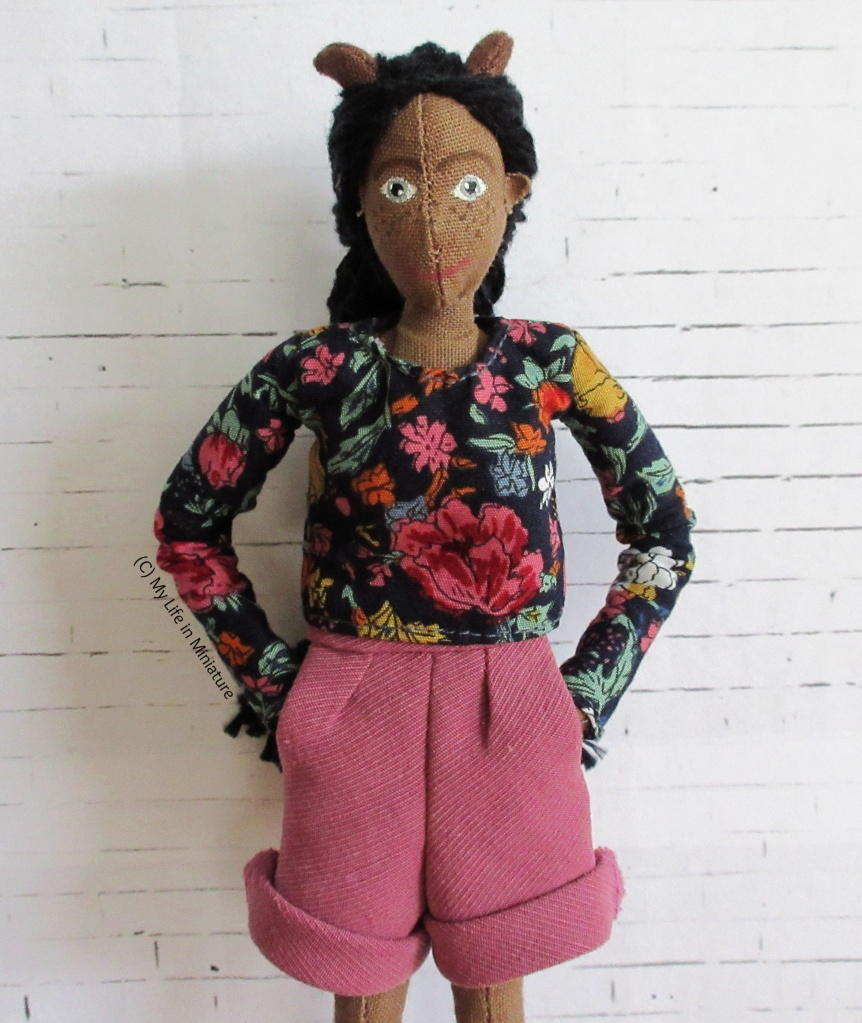 Petra wears a long-sleeved navy top with pink, red, yellow and white flowers on, and her pink corduroy shorts. Her hands are in her pockets and she smiles at the camera.