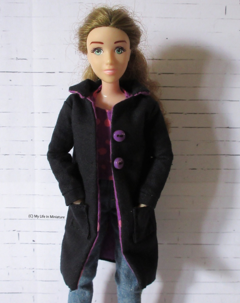 Sarah wears a black, knee-length coat over a t-shirt and a pair of jeans. The coat has a collar, two purple buttons on the front, and pockets, which Sarah's hands are in. She smiles at the camera.
