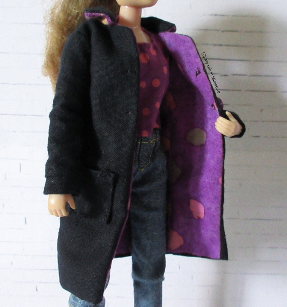 Sarah holds the coat open to show the purple lining. Two stitches on the opposite front panel to the buttons are visible, acting as fake buttonholes.