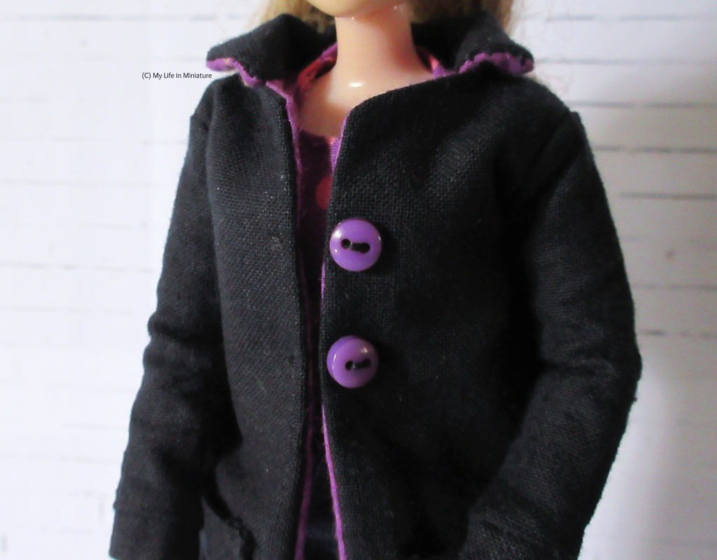 Close-up of the top front of the coat, with the buttons and collar clearly visible. The underside of the collar is in the same purple fabric as the lining.