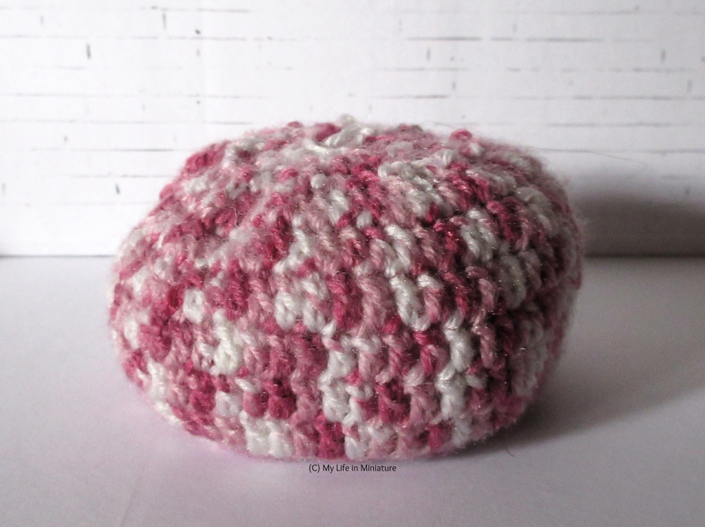 A miniature crocheted pouf sits against a white brick background. It is white and various shades of pink with a flat base.