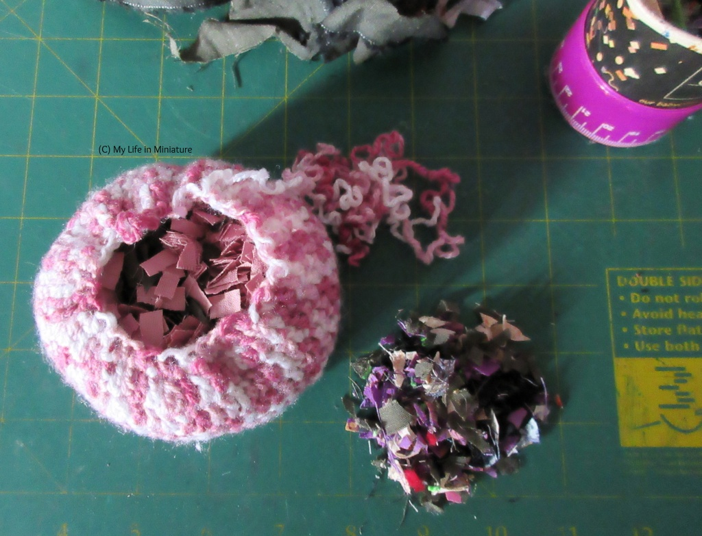 A pink crocheted pouf sits on a craft mat, the centre unravelled so that the stuffing is visible. The stuffing is small squares of scrap fabric, with a small pile of it beside the pouf.