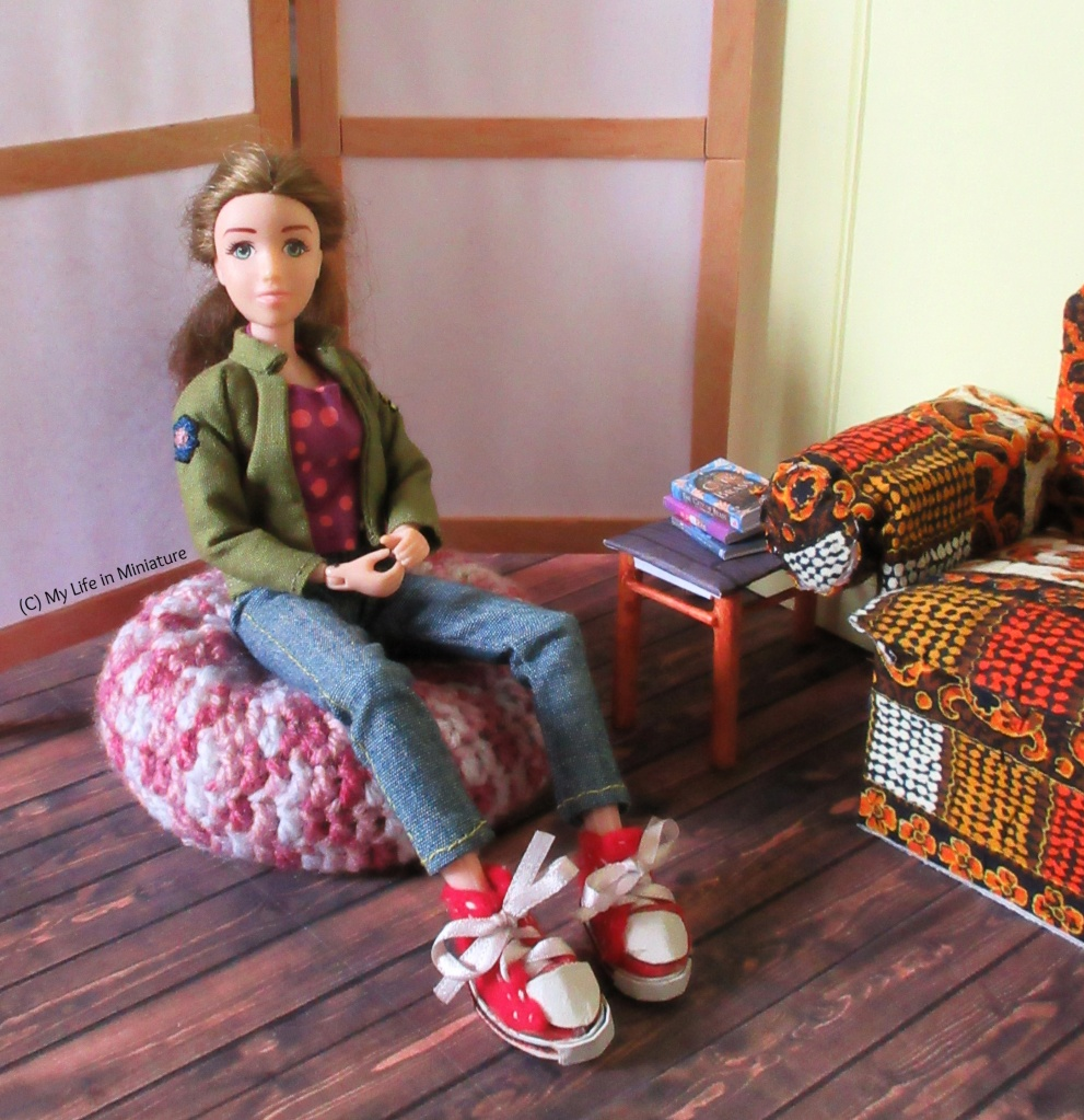 Sarah sits on the beanbag, smiling at the camera. The armchair is in the right of frame, and the side-table with its stack of books is visible.