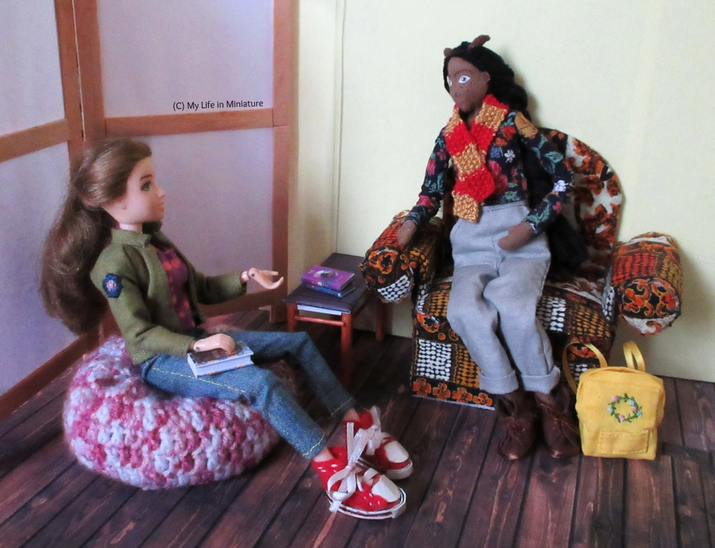 Sarah sits on the beanbag, a book in her lap and gesturing in conversation with Petra. Petra sits on the armchair, legs tucked under, listening to Sarah. Petra's backpack sits at her feet.