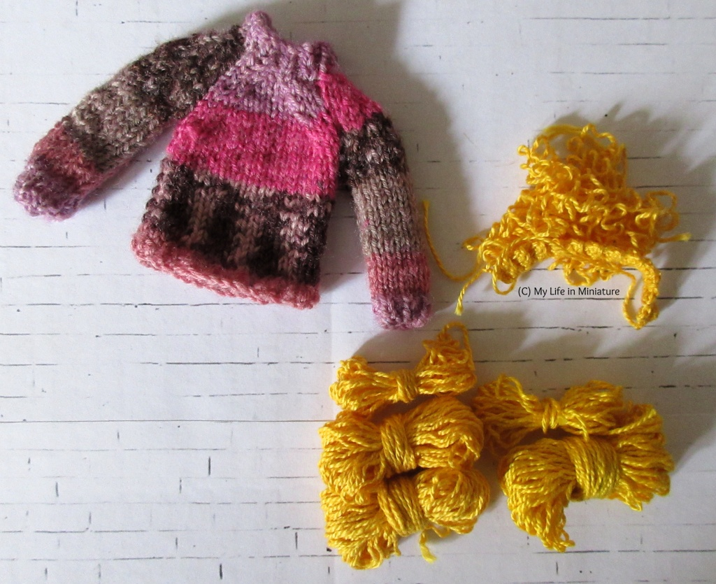 Petra's pink jumper sits on a white brick background. Next to it are five small skeins of wrinkled yellow yarn, and a small pile of the same yarn.