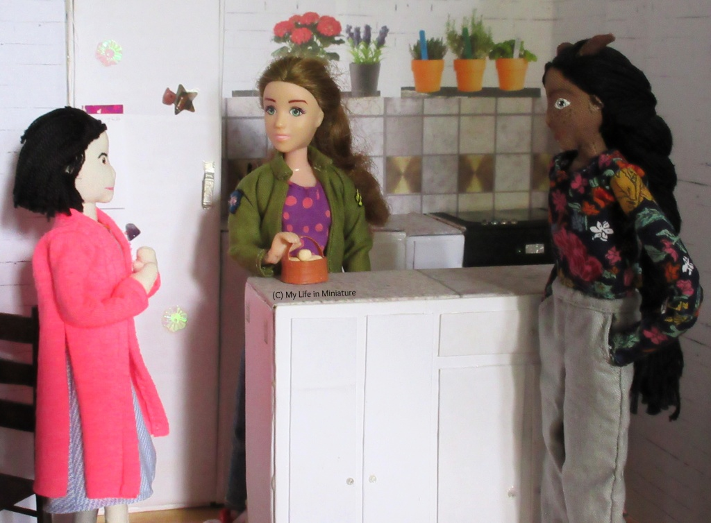 Sarah, Tiffany and Petra stand in Sarah's kitchen. Sarah is behind the island, hand on the handle of a basket of plain eggs. Tiffany is to the left, hands clasped, talking to Sarah. Petra is to the right, looking past Tiffany to the table.