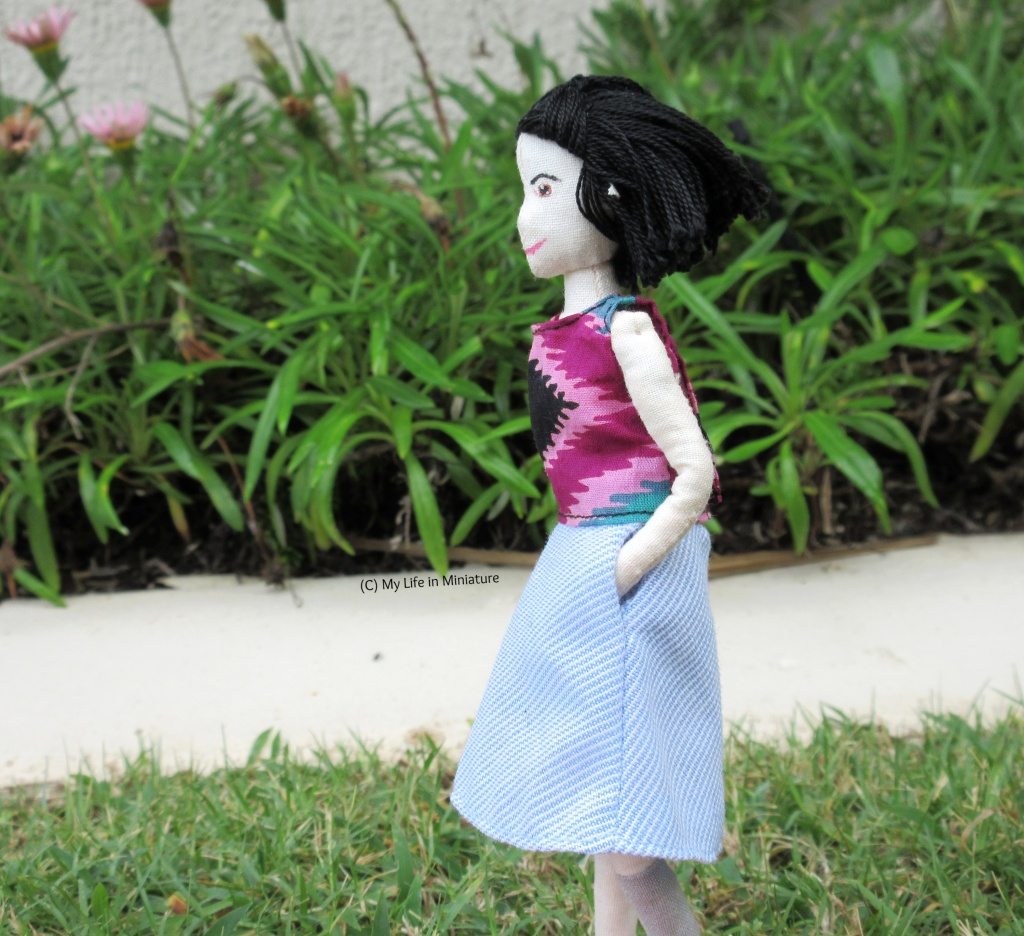 Tiffany stands on grass, next to a flower bed. She wears the tie-dyed shirt with a blue-and-white-striped skirt, hands in pockets. She faces the left, and her hair is blown in the wind behind her.