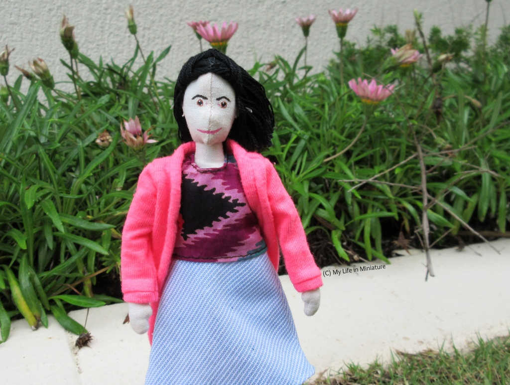 Tiffany stands on grass, in front of a flower bed. She wears the tie-dyed shirt and blue skirt, with her pink cardigan over the top. She faces the camera, hair being windblown to the right.