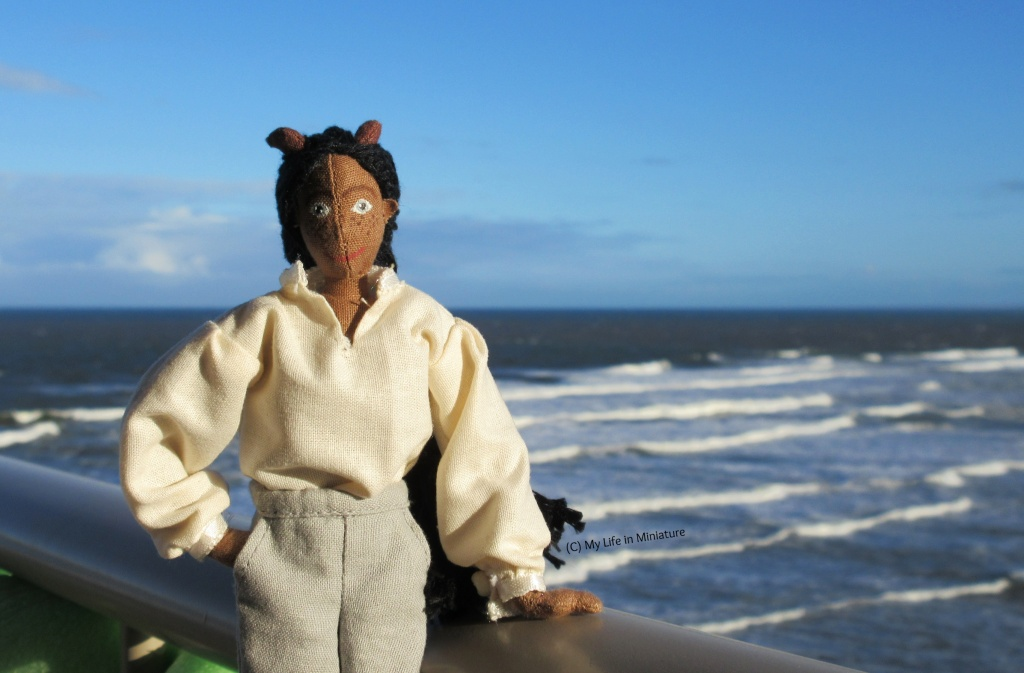 Petra stands at a railing, overlooking the sea with waves crashing behind her. She wears the 'pirate' shirt, has a hand on the railing, and is smiling at the camera.