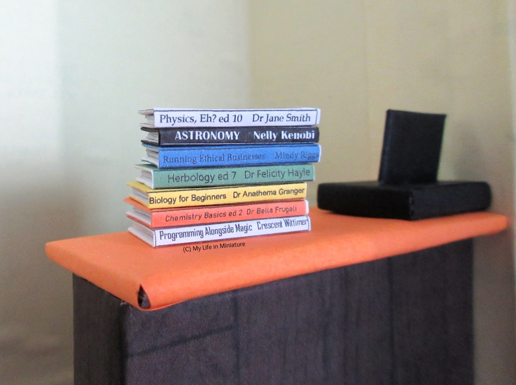 A stack of textbooks sits on the front counter of the Palace Library. They are for topics like physics, astronomy, business, herbology, biology, chemistry, and programming.