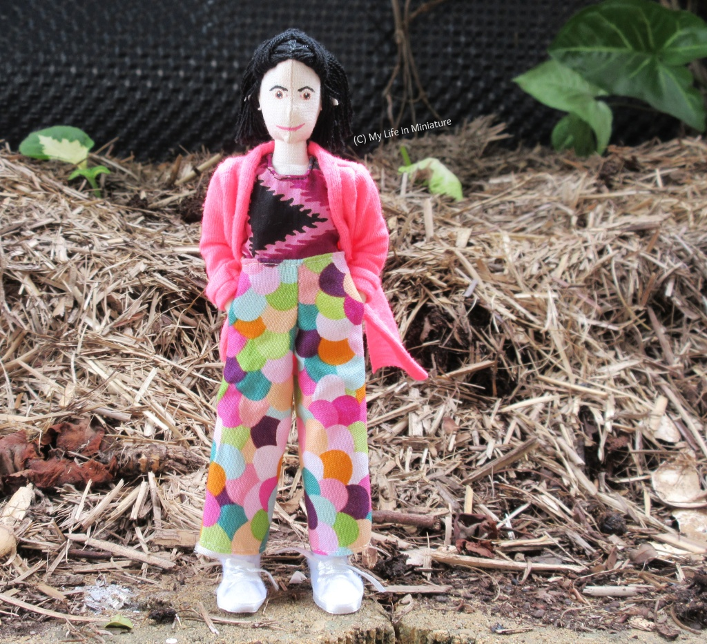 Tiffany stands on a brick on the edge of a mulched garden bed. She wears her multi-coloured pants with a purple tie-dyed shirt and a hot pink cardigan. Her hands are in the pant pockets, and she smiles at the camera.