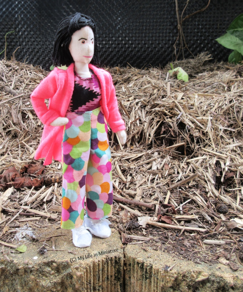 Tiffany stands on a brick on the edge of a mulched garden bed. She wears her multi-coloured pants with a purple tie-dyed shirt and a hot pink cardigan. She is placing one hand on her hip, and is about to walk to the right, looking in that direction.
