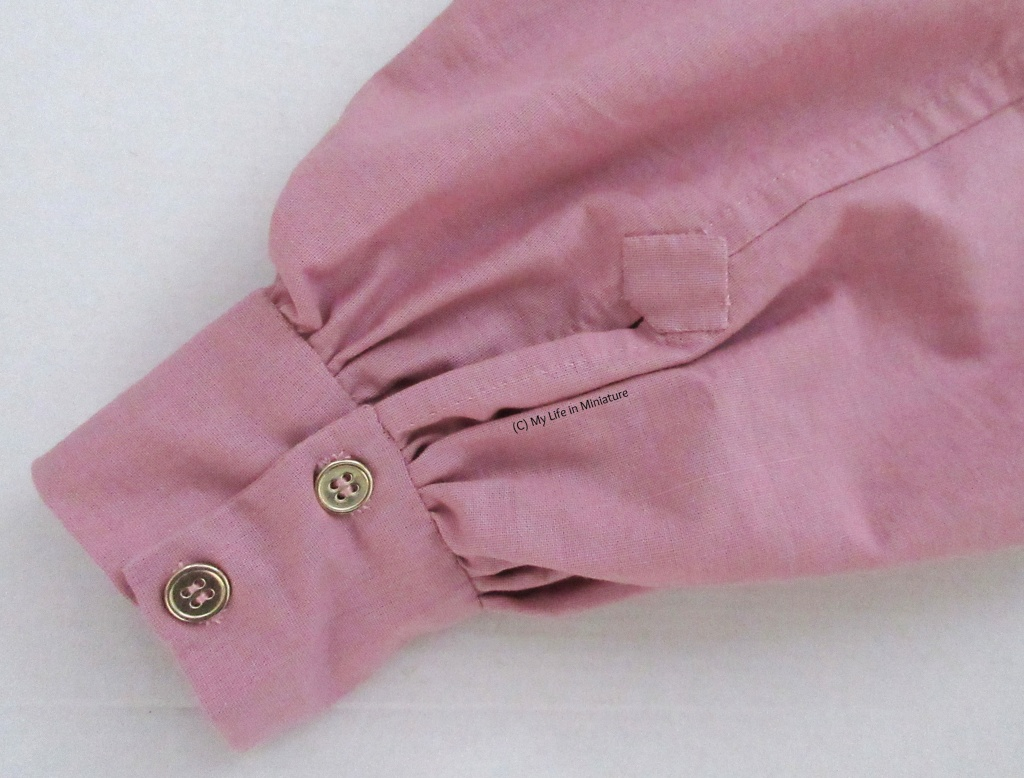 Close-up of a cuff of the dusky pink 'pirate' shirt. Two gold buttons hold it closed, the gathering is visible, and a reinforcement patch is at the base of the cuff slit.