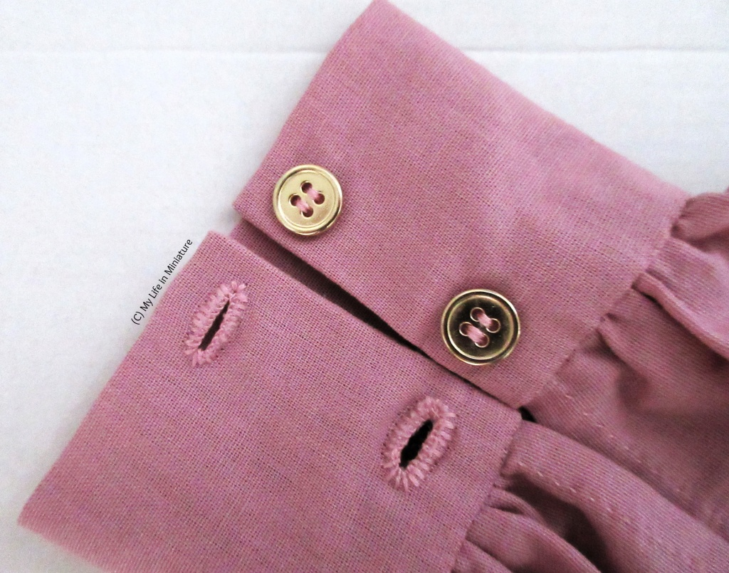 Close-up of the buttons and buttonholes of the cuff. Two hand-sewn buttonholes are on the opposite cuff edge to the gold buttons. The holes are sewn in a slightly paler pink than the fabric.