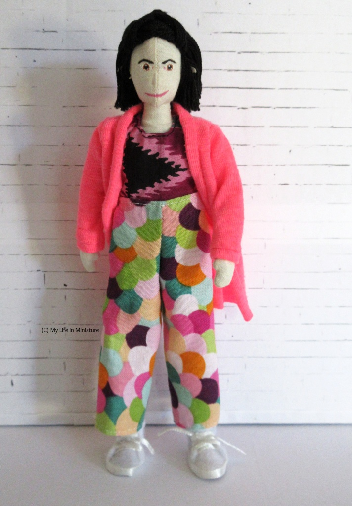 Tiffany wears wide-legged pants in a multi-coloured scalloped fabric. She wears them with a purple tie-dyed shirt and a hot pink cardigan.