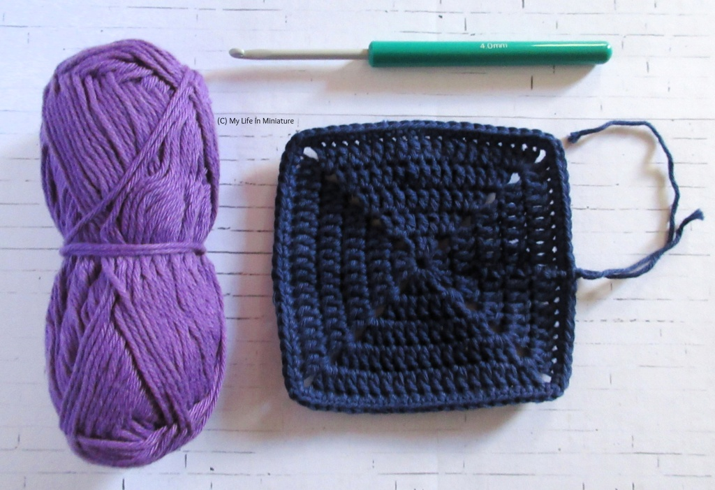 A solid navy crocheted square sits on a white brick background, ends visible. Above it is a 4mm crochet hook, and to its left is a ball of light purple cotton yarn.