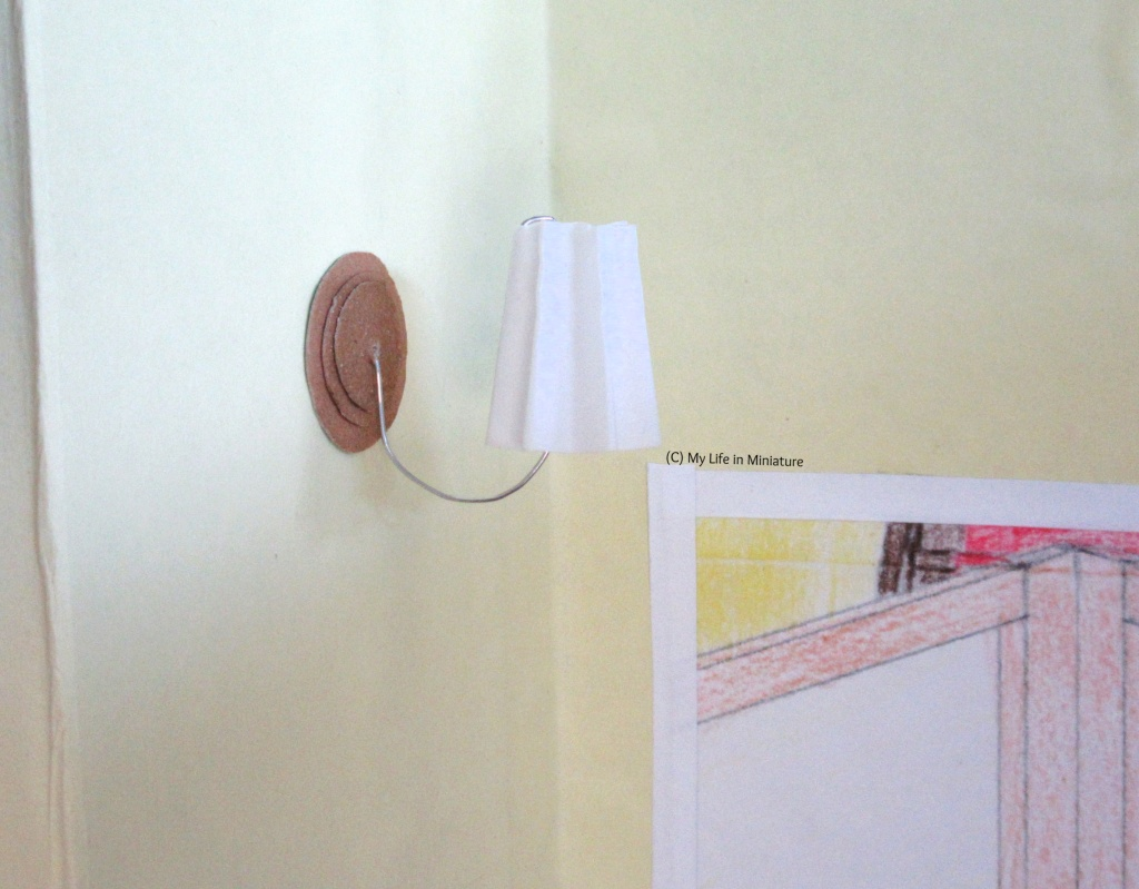 Close-up of one of the lights in the last image. They have a white concertina-d lampshade, attached to the wall with a smile-shaped loop of silver wire. The wall fitting is three brown circles, stacked smallest to largest. The corner of the doorway is visible in the bottom right.