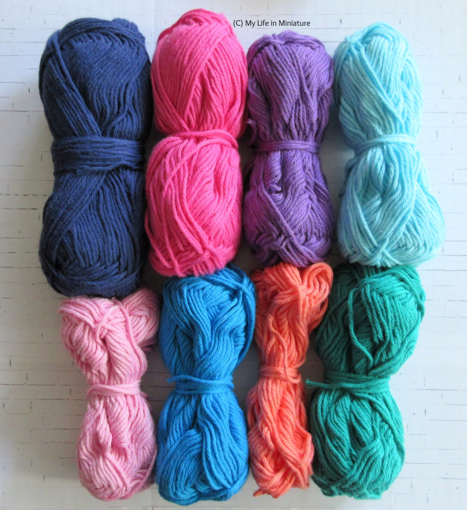 Eight balls of yarn in two rows of four sit on a white brick background. Top row, left to right, has navy blue, bright pink, purple, and pale blue balls. Bottom row, left to right, has pale pink, bright blue, peach, and emerald green.