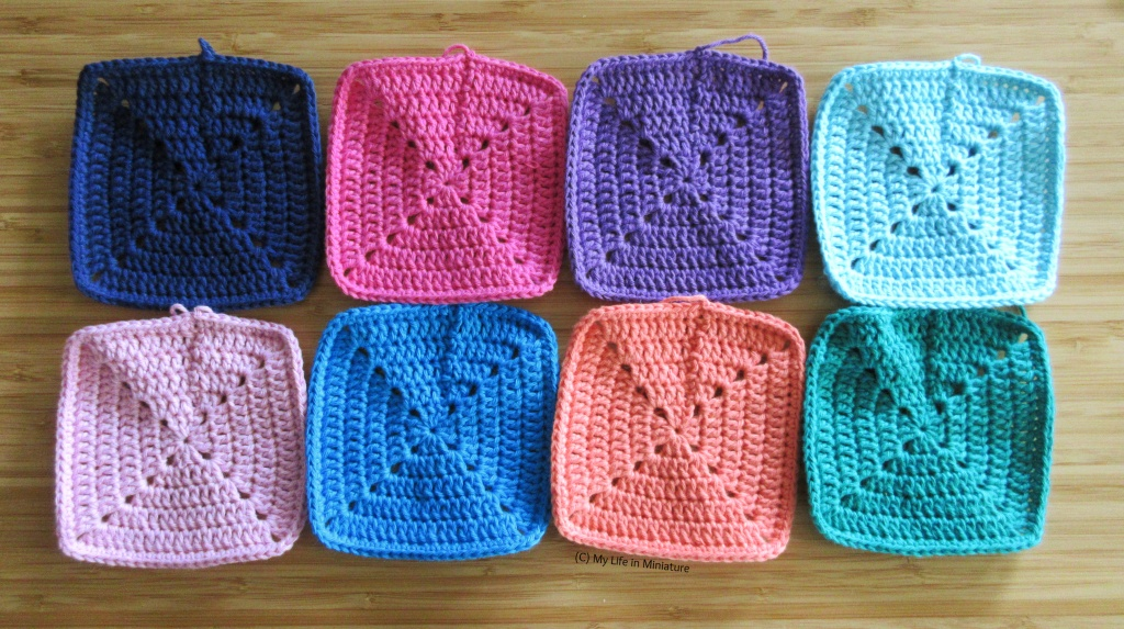 Eight crochet squares sit in two rows of four on a wood background. The colours are (top-bottom, left-right) navy, pink, purple, pale blue, pale pink, blue, peach, and green.