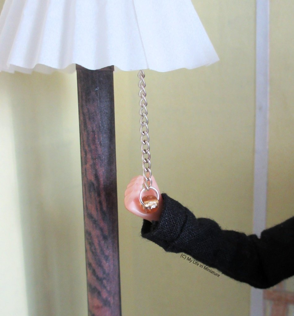 Close-up of the chain hanging from beneath the lampshade of the floor lamp. Sarah's hand cups the gold bead on the end of the chain.