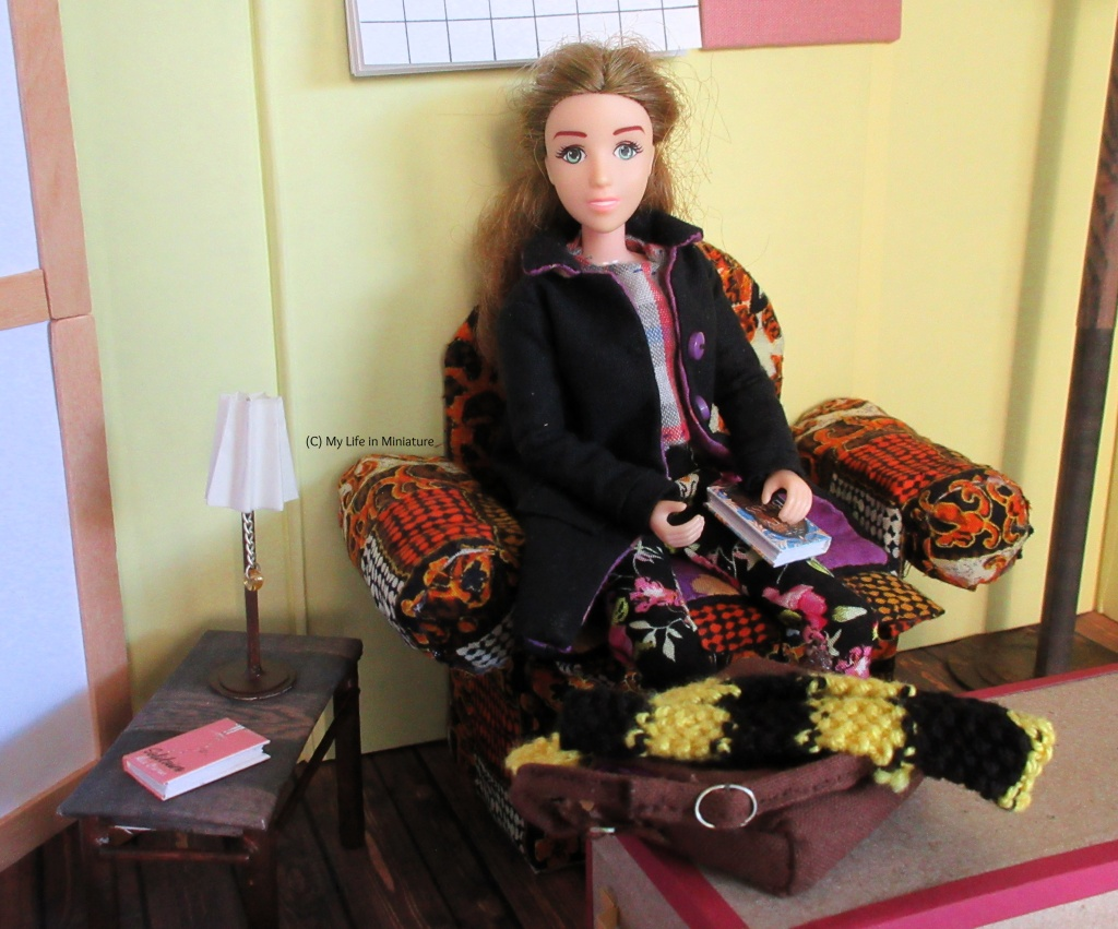 Sarah sits in the armchair with her bag and scarf on the trunk in front. She has a book on her lap, and is smiling at the camera. The side table is visible, with the lamp and another book on it.