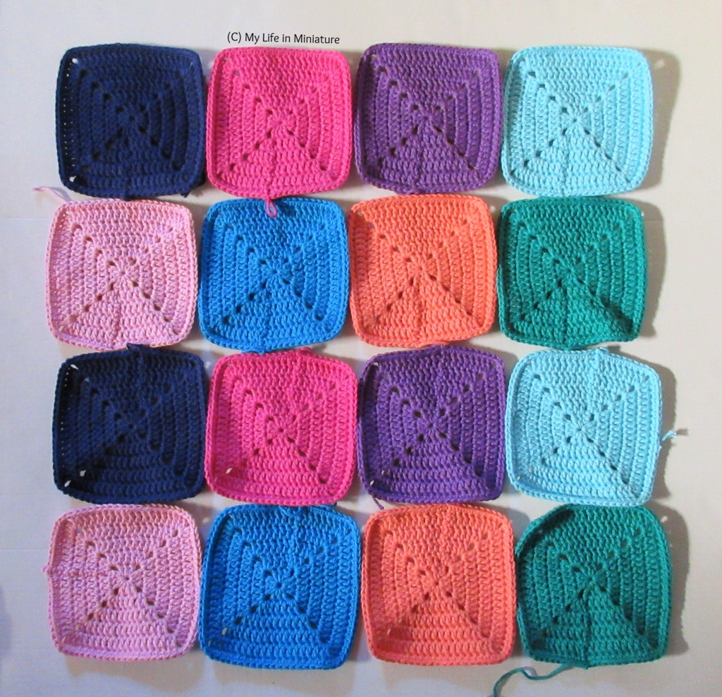 Sixteen squares of crochet are laid out on a white background. The first row's colours are (left to right) navy, pink, purple, and pale blue. The second row's colours are (left to right) pale pink, blue, peach, and green. The two rows are repeated in the third and fourth rows respectively.