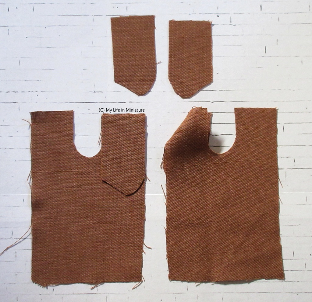 Five pattern pieces for a pocketed pair of miniature pants are laid out on a white brick background. The fabric is a rust-brown colour, and one pocket front is sewn to one pant piece.