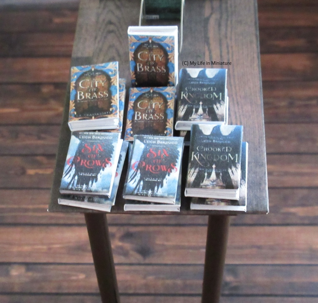 Close-up of one end of the small table. Six stacks of books are on the table, with one book on a wire book stand behind them.