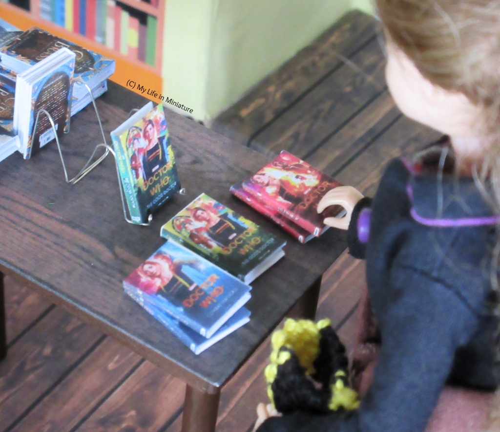 The other end of the small table. There are three stacks of Thirteenth Doctor novels on the table, with one on a wire book stand. The shot is over Sarah's shoulder, and she has a hand on one of the books.