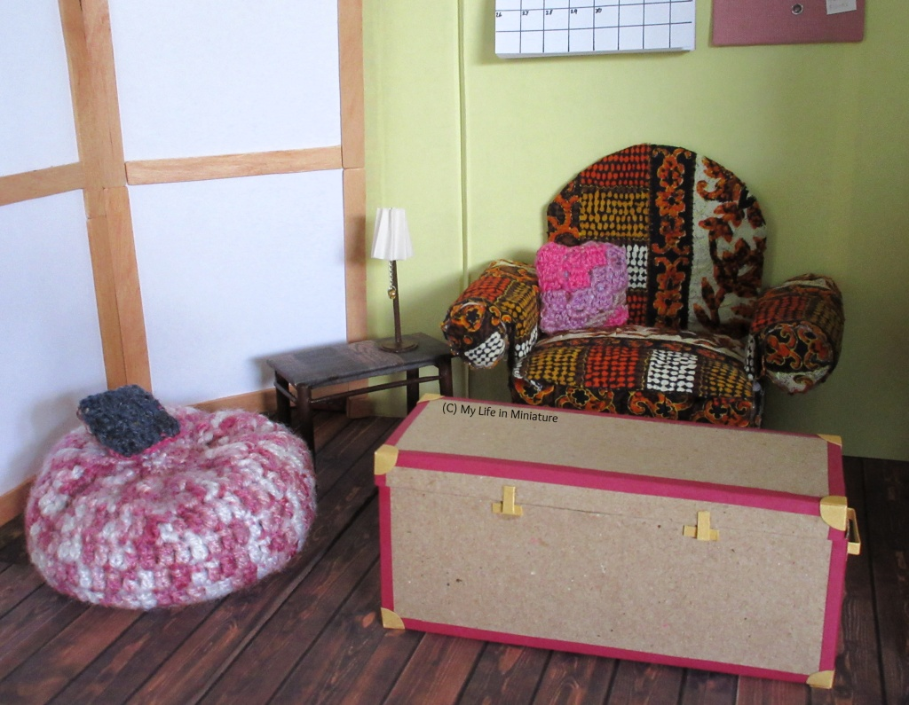 The upstairs room of the Palace Library. The armchair and beanbag are visible, as is the small side table and trunk/coffee table. On the armchair is a square pink, purple and grey crocheted cushion. On the beanbag is a smaller square navy blue crocheted cushion.