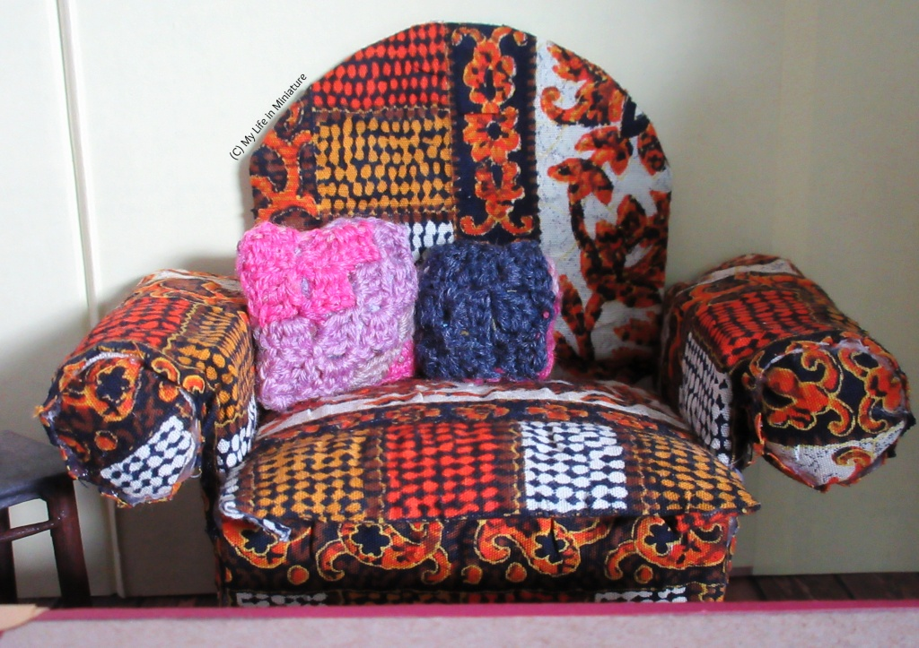 Close-up of the armchair, which has two cushions on. The larger cushion is pink, purple, and grey, crocheted in a corner-to-corner style, which looks like very large pixels. The smaller navy blue cushion is crocheted in the same style, and has a pink back.
