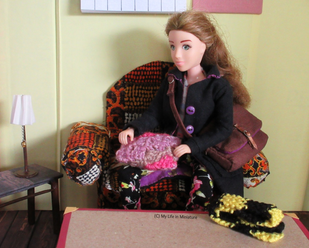 Sarah - in her coat, with her bag - sits on the armchair, with the larger pink/purple/grey crocheted cushion on her lap. She is looking at it, running a hand over the stitches.