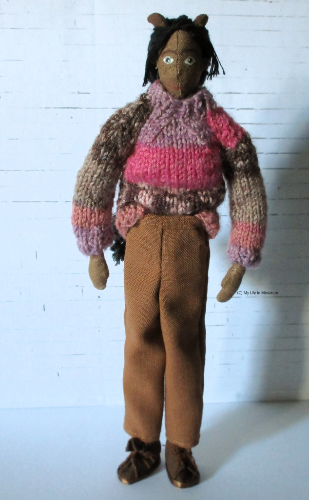 Petra stands in front of a white brick background. She wears a pair of brown loose-fitting pants with her pink jumper and dark brown shoes. She smiles at the camera.