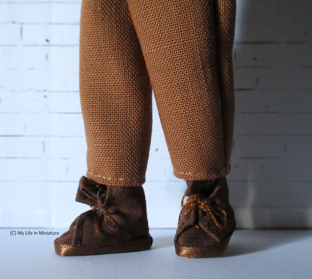 Close-up of the hems at the bottom of the legs of the pants, with Petra's brown shoes also visible.