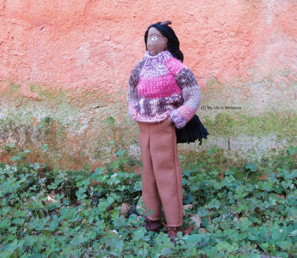 Petra stands outside in a patch of clover, against a terracotta background with green algae (?) on. She wears the brown pants and pink jumper, and has her hands in her pockets. She looks up towards the left of the image.