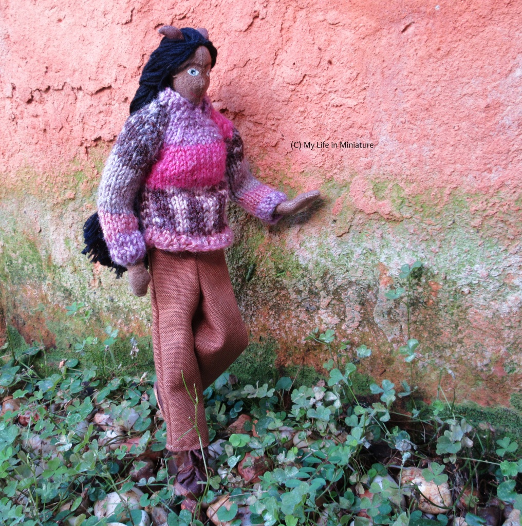Petra walks in the patch of clover, one hand on the terracotta wall for stability. She is looking down at where she is walking, and wears the brown pants and pink jumper.