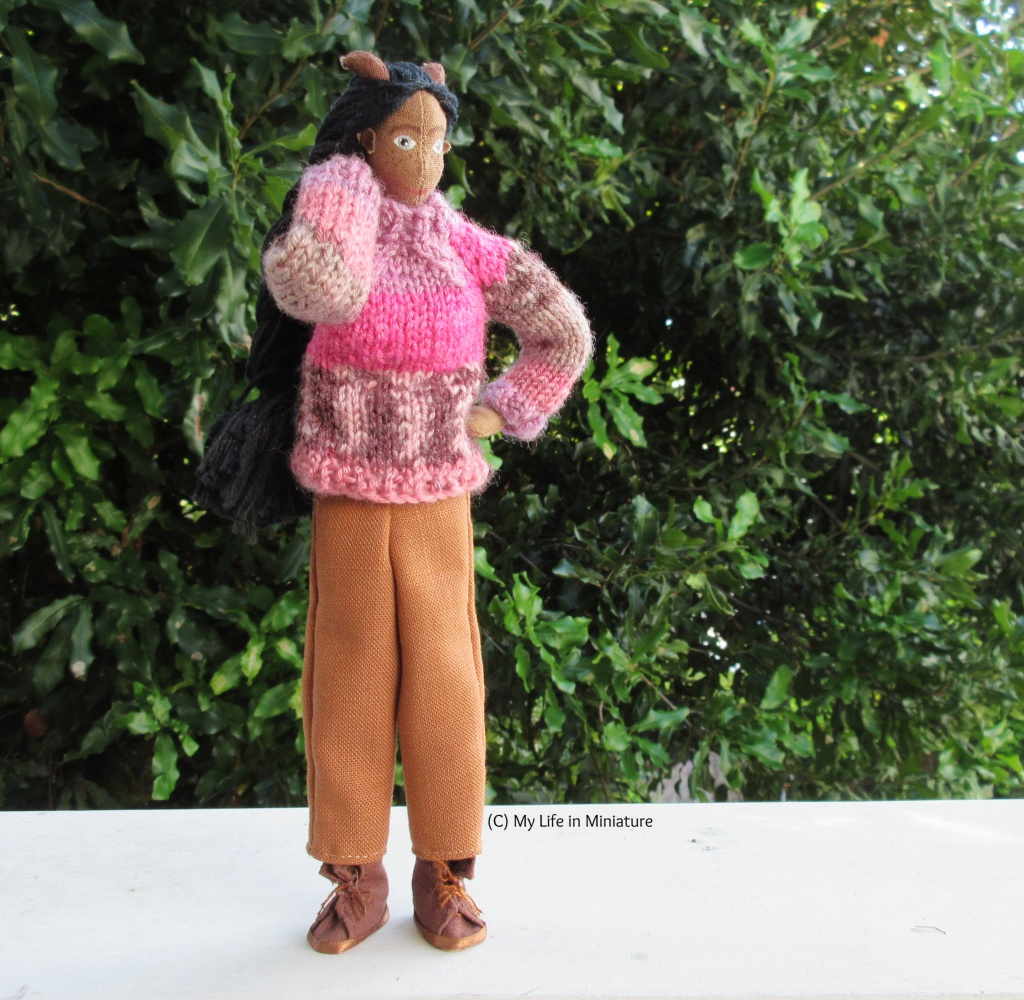 Petra stands against a large green bush, wearing the brown pants and her pink jumper. She has one hand behind her neck and the other on her hip, and is looking to the right.