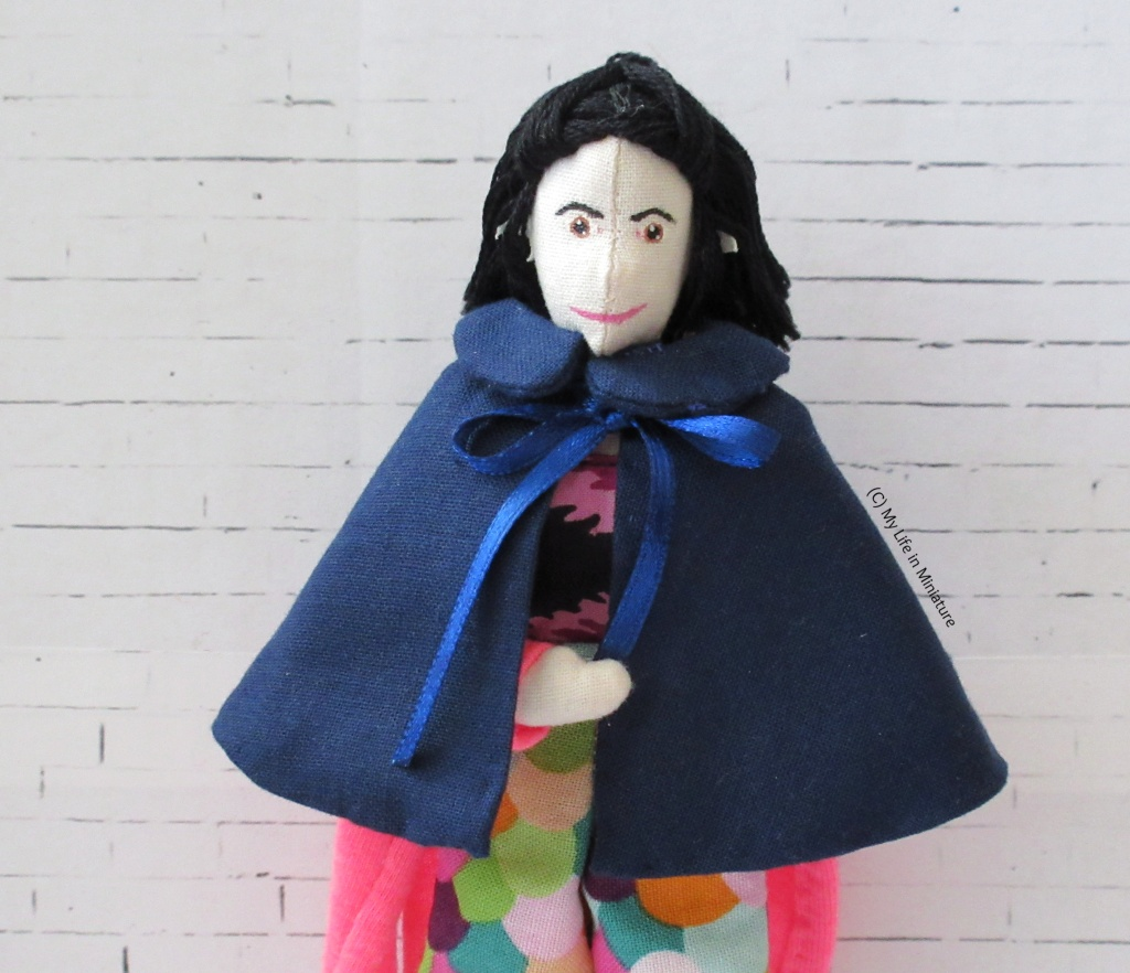 Tiffany stands against a white brick background. She has a navy cape tied around her shoulders. The cape is about wrist-length, with navy ribbon ties and a Peter Pan style collar.