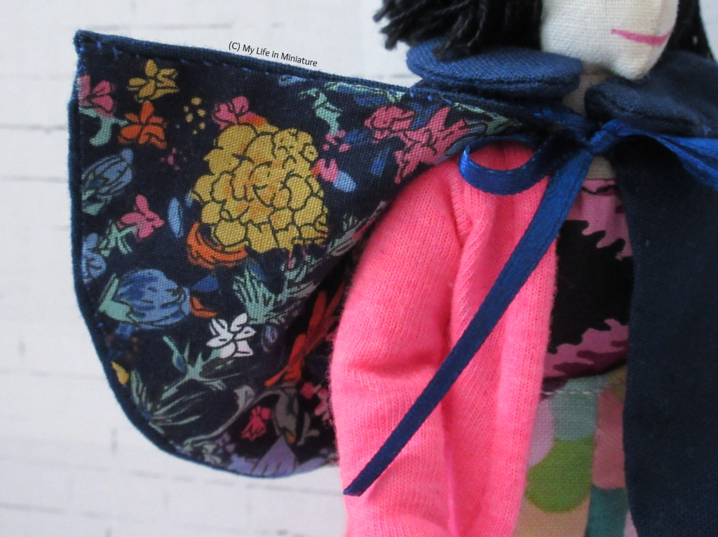 Close-up of one corner of the cape, which has been flipped up to show a floral lining. The flowers are blue, pink, and yellow, with green foliage, all on a navy background. Tiffany's pink-cardigan-clad shoulder is also visible.