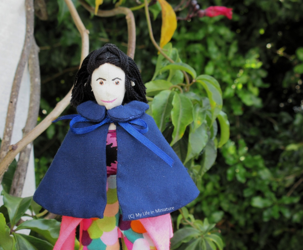 Tiffany stands near a white wooden post, which has a vine growing up it. She wears the navy cape, tied with a bow in the front. She has her hands in her pockets and is smiling at the camera. In the background is some leaves from the vine, and a large bush.