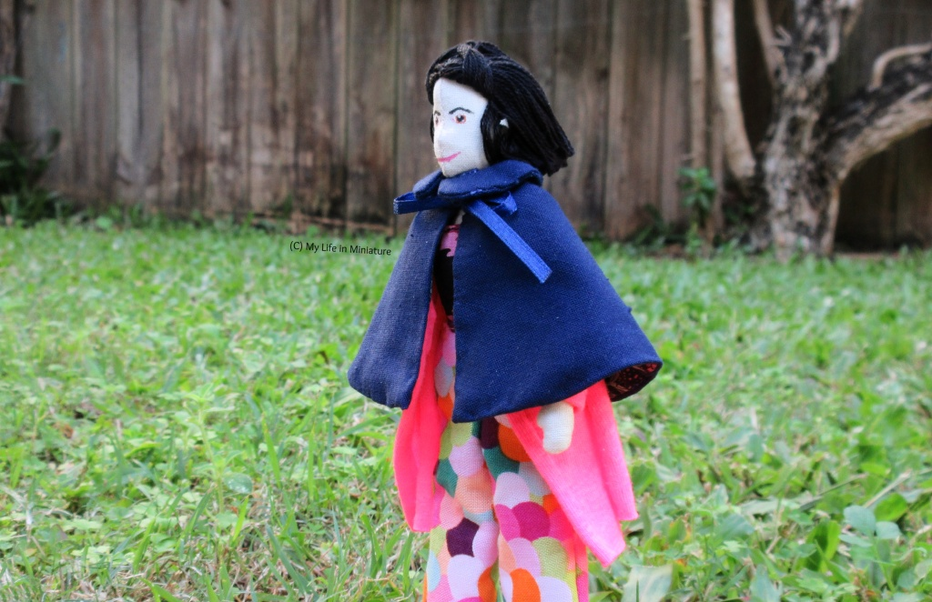 Tiffany stands in a 'field', and in the background is a wooden fence and a gnarled tree trunk. She wears the navy cape over her hot pink cardigan and colourful pants. Her body is angled to the left, which is also the direction she's looking.