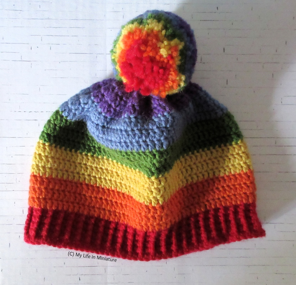 A rainbow-striped crocheted beanie with a rainbow-striped pompom sits flat-ish on a white brick background. The stripes are in rainbow order up from the ribbing.