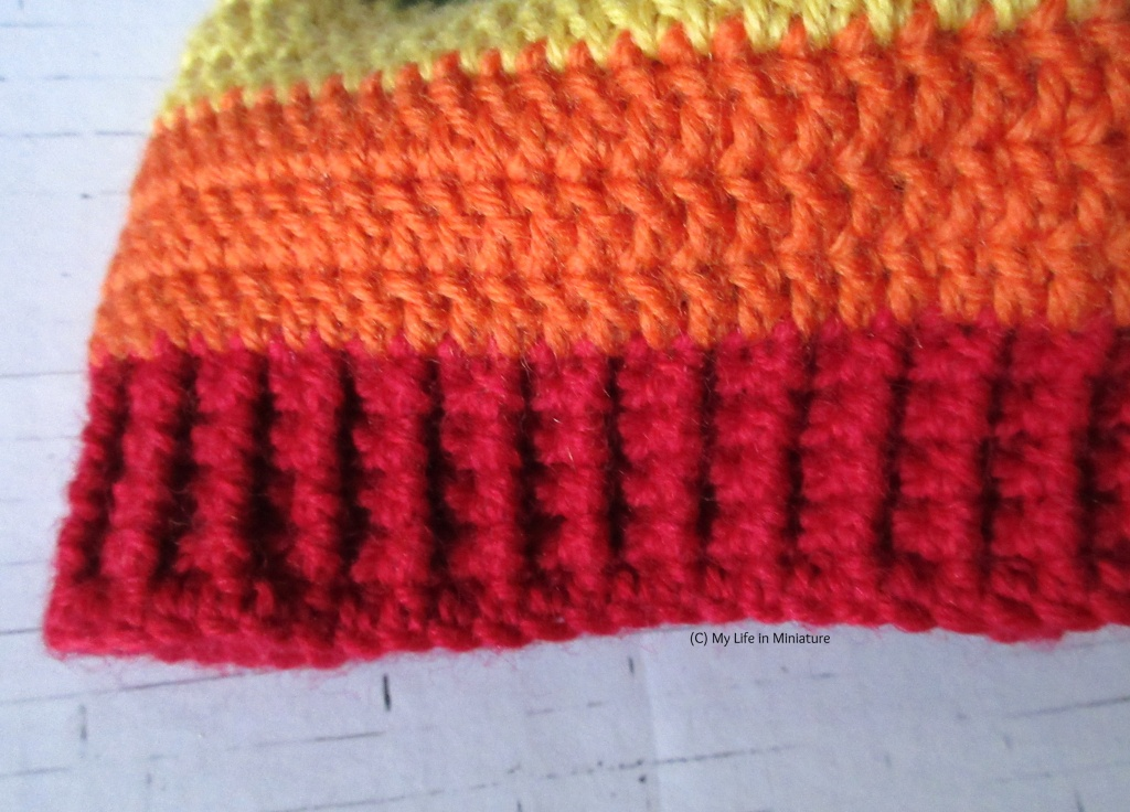 Close-up of the red ribbing of the rainbow-striped beanie on a white brick background. The treble crocheted orange stripe above the ribbing is also visible.
