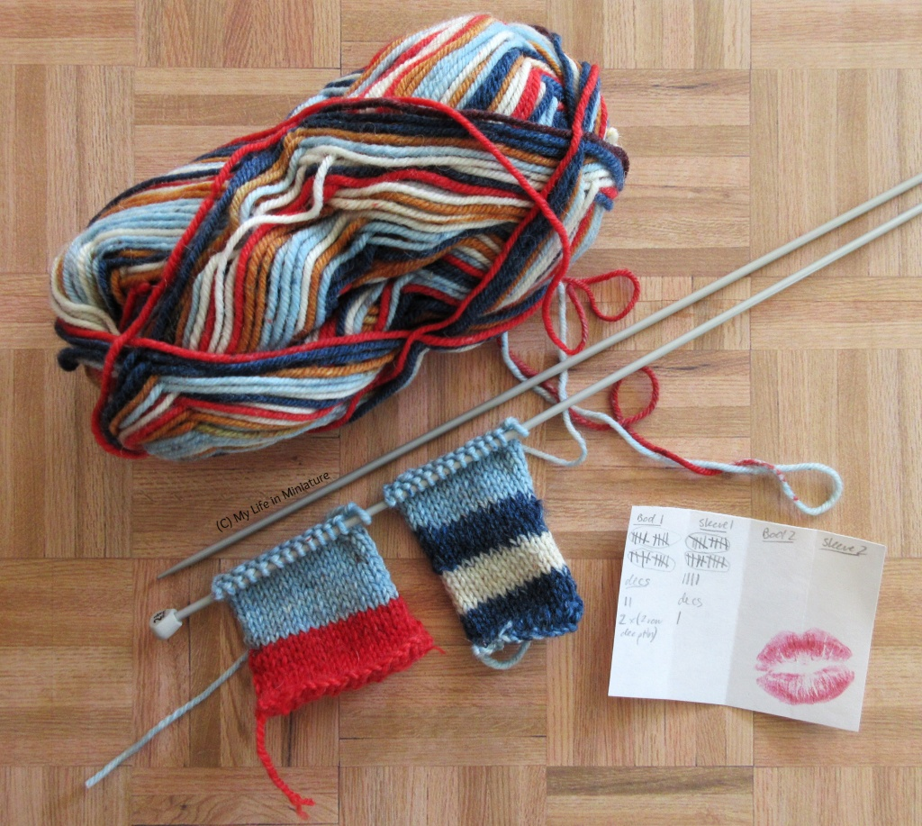 A ball of yarn, two knitting needles, two small pieces of knitting, and a sticky note sit on a wood background. The yarn is multicoloured: red, dark and light blue, white, and pale brown.