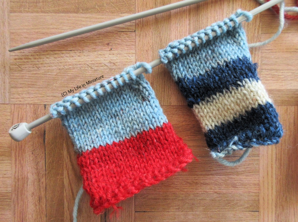 Close-up of the two small pieces of knitting on the knitting needles. The piece on the left is half red, half pale blue. The piece on the right is striped dark blue, white, dark blue again, and pale blue. They are on a wood background.