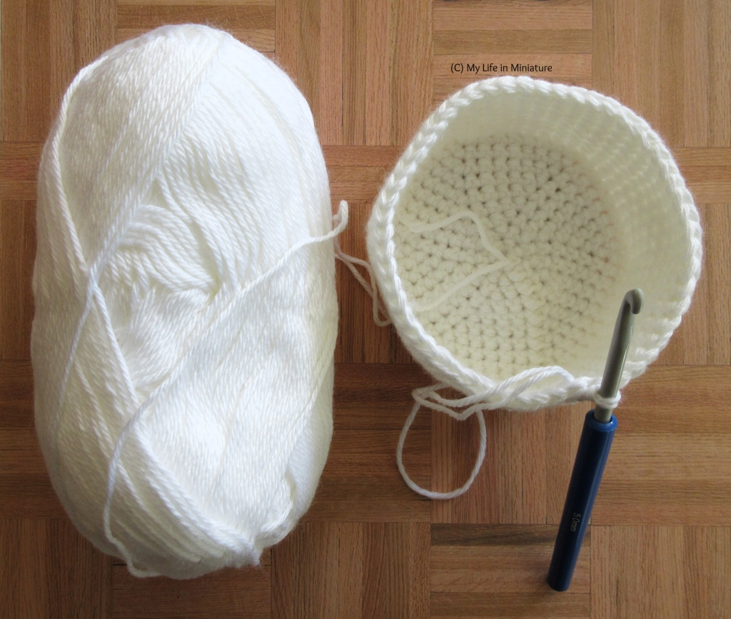 A large ball of white yarn and a round crocheted nest sit on a wood background. The nest has a crochet hook leaning against it in the working loop.